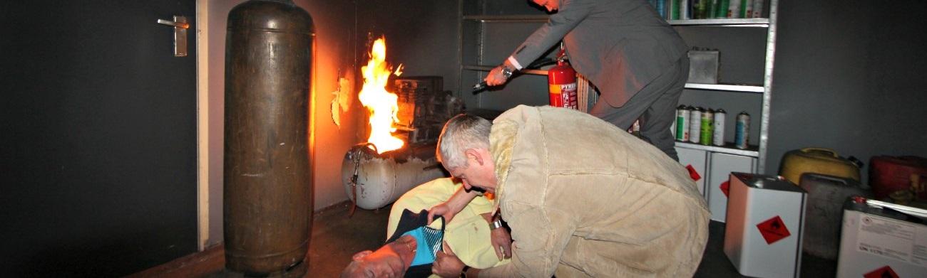 Twee cursisten. Één blust een brand de andere redt het slachtoffer tijdens een BHV cursus