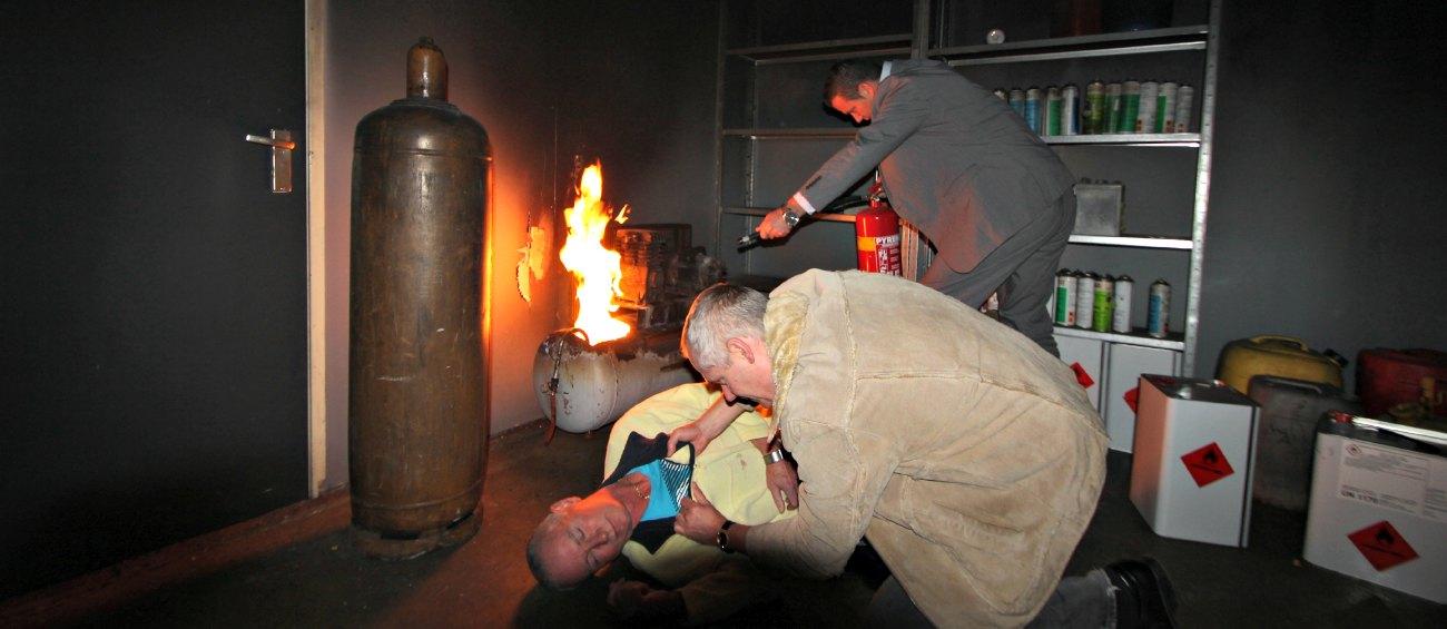 Twee cursisten. Één blust een brand de andere redt het slachtoffer tijdens een Basis BHV cursus